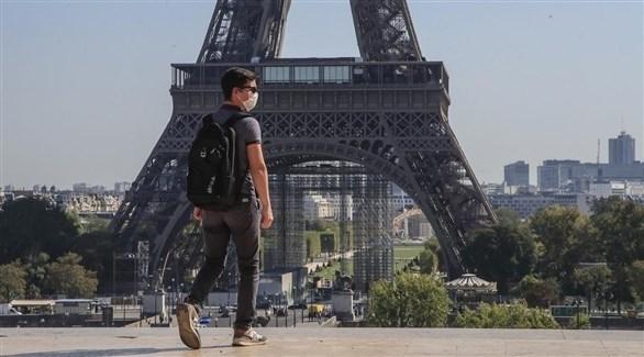 شخص يرتدي كمامة بالقرب من برج إيفل (أرشيف)