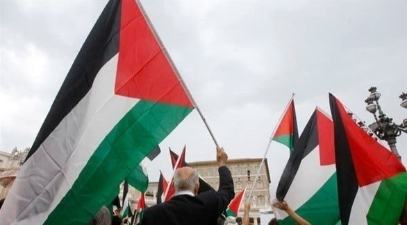 رفع مجموعة من الأعلام الفلسطينية خلال أحد التجمعات (أرشيف)