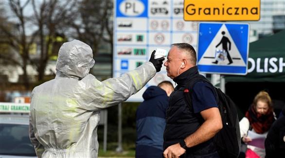 عامل في القطاع الصحي يفحص بولونيا على الحدود بين البلدين (أرشيف)