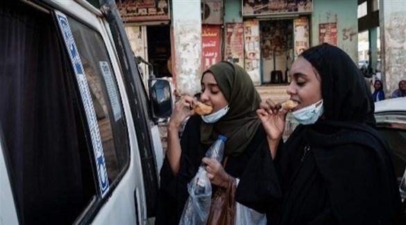 سودانيتان تتناولان خبزاً تقليدياً في اليوم الذي أعلن فيه شطب اسم بلادهما من قائمة الإرهاب (أ ف ب)
