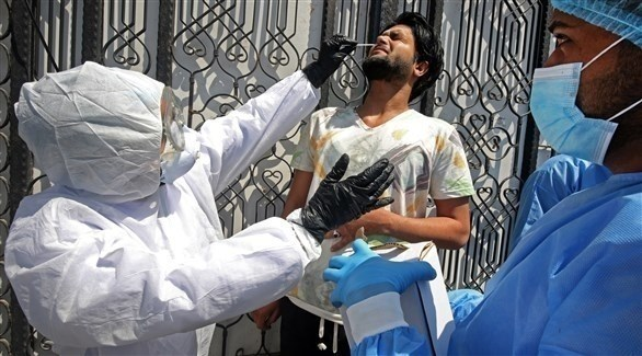 ممارس صحي يفحص درجة حرارة  أحد المواطنيين في العراق (أرشيف)