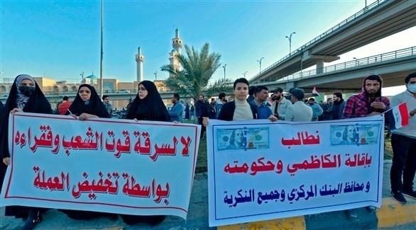 متظاهرون في النجف يرفعون شعارات رافضة لقرار تخفيض قيمة الدينار العراقي (الفرنسية)