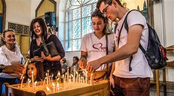 مسيحيون سوريون يوقدون شموعاً في كنيسة (أرشيف)