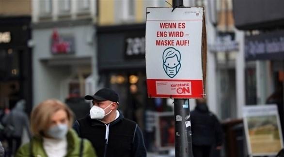 مواطنون يسيرون بجوار لوحة إرشادية تحث على التزام الإجراءات الوقائية (أرشيف)