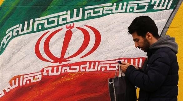 رجل يمر بجانب جدارية للعلم الإيراني (أرشيف)