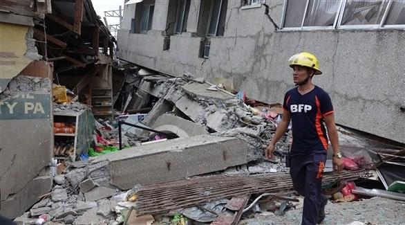 عامل في الدفاع المدني الفلبيني يمشي فوق ركام ناجم عن زلزال (أرشيف)
