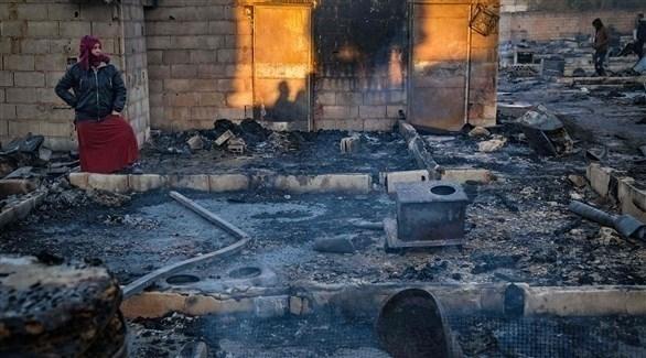 لاجئة تعاين ما خلفه الحريق بالمخيم في لبنان (أ ف ب)