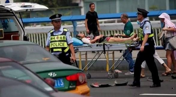 مسعف ينقل مصاباً في هجوم الأحد بحضور عناصر من الشرطة الصينية (تويتر)