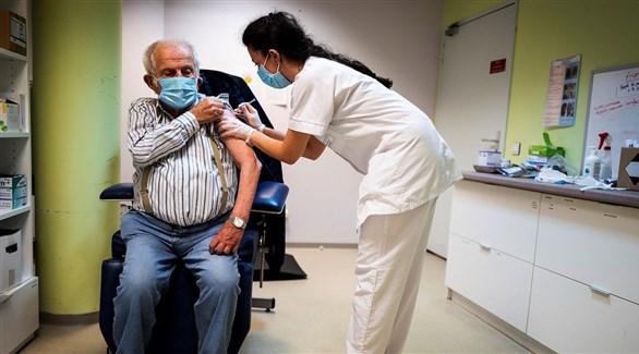 ممرضة فرنسية تطعم مسناً ضد كورونا (أرشيف)