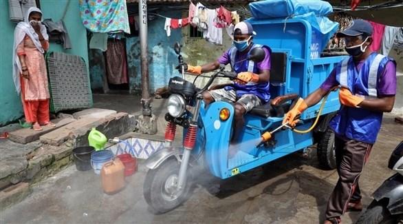 عاملان هنديان يعقمان شارعاً في منطقة شعبية (أرشيف)