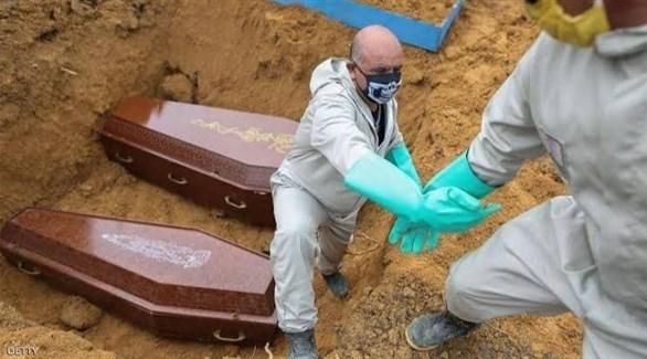 عاملان في مقبرة برازيلية أثناء دفن ضحيتين لكورونا (أرشيف)
