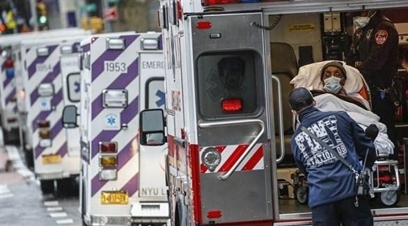 مسعف أمريكي يساعد مصاب بكورونا في سيارة إسعاف (أرشيف)