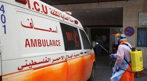 عامل أثناء تعقيم سيارة إسعاف للهلال الأحمر الفلسطيني (أرشيف)