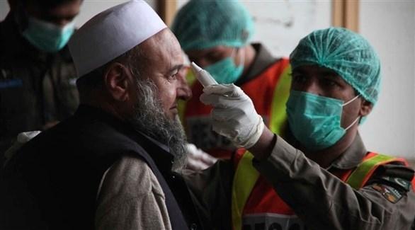 فحوصات احترازية لمواطن باكستاني ضمن جهود السيطرة على كورونا (أ ف ب)