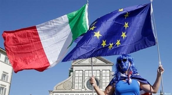شخص يرفع علم الاتحاد الأوروبي والعلم الإيطالي (أرشيف)