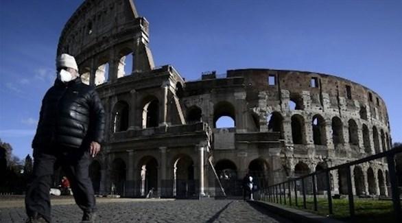 إيطالي يسير بجوار مبنى الكولوسيوم الشهير في روما (أرشيف)