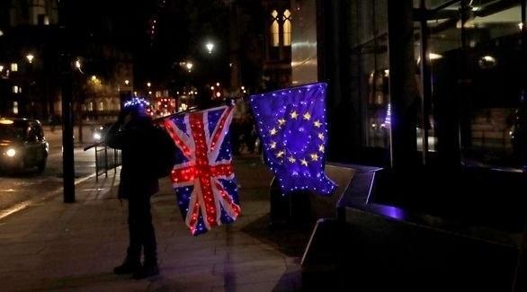 شخص يحمل علم الاتحاد الأوروبي وعلم البريطاني (أرشيف)