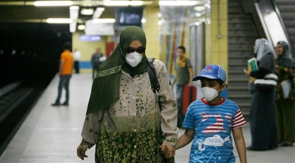 سيدة مصرية وطفلها يرتديان الكمامات للوقاية من كورونا (أرشيف)