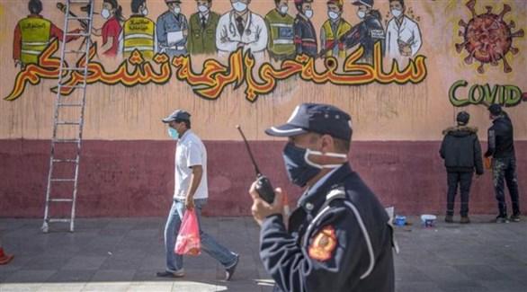 شرطي مغربي ومدنيين أمام جدارية لشكر العاملين في القطاع الصحي (أرشيف)