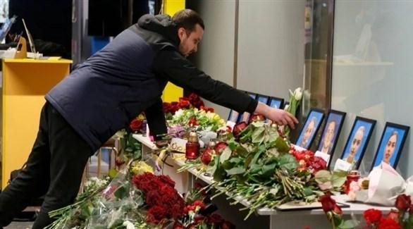 ورود ورسائل وضعت إلى جانب صور العاملين في الطائرة المنكوبة، داخل مطار كييف (أ ب)