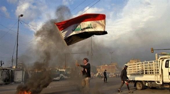 متظاهر يرفع العلم العراقي وسط الشارع (أرشيف)