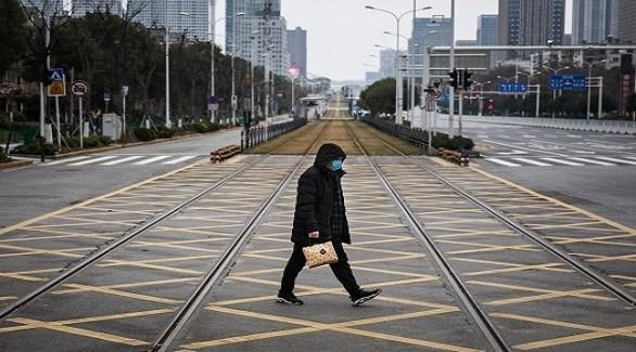 صيني يعبر شارعاً خالياً من الحركة بعد تشديد القيود الرسمية لمكافحة الفيروس (أرشيف)