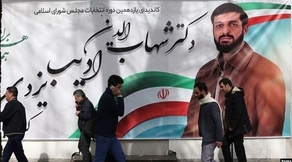 إيرانيون أمام ملصق انتخابي لأحد المرشحين للبرلمان (الحرة)