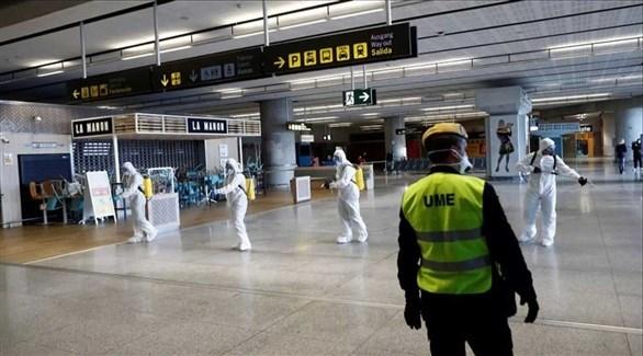 شرطي يراقبون عاملين يعقمون قاعة خالية من المسافرين في مطار إسباني (أرشيف)