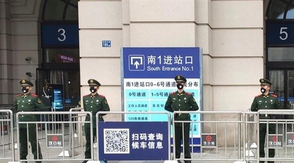 عناصر من الشرطة الصينية أمام محطة القطارات المركزية في مدينة ووهان (أرشيف)
