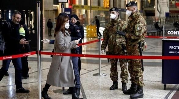جنديان إيطاليان يراقبان حركة المسافرين في محطة ميلانو للقطارات (أنسا)