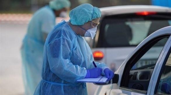 طبيبة تسجل بيانات سائق مركبة ضمن إجراءات فحص الألمانيين من كورونا أرشيف)