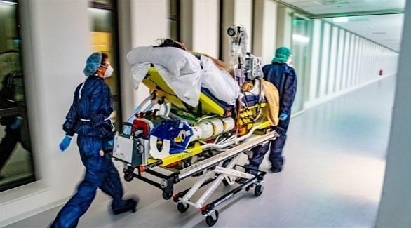 مسعفان ينقلان مصاباً بكورونا للعلاج (أرشيف)