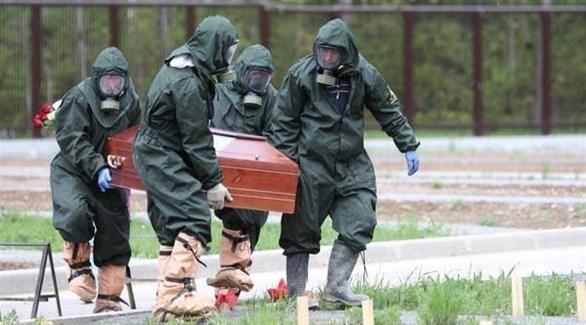عاملون بقطاع الصحة الروسي ينقلون تابوت متوفى بكورونا للمقبرة (أرشيف)