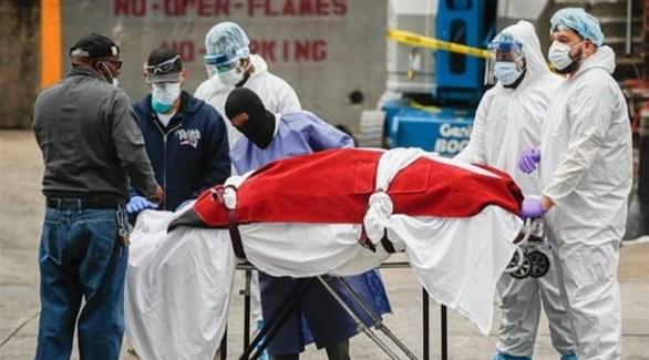 عاملون في القطاع الصحي الأمريكي ينقلون جثة أحد ضحايا كورونا (أرشيف)