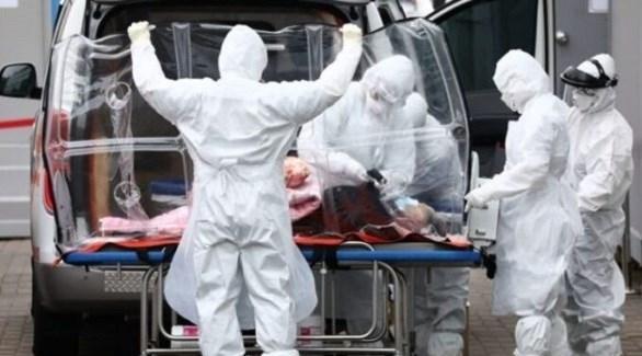 مسعفون ينقلون مصاباً بكورونا لسيارة إسعاف (أرشيف)