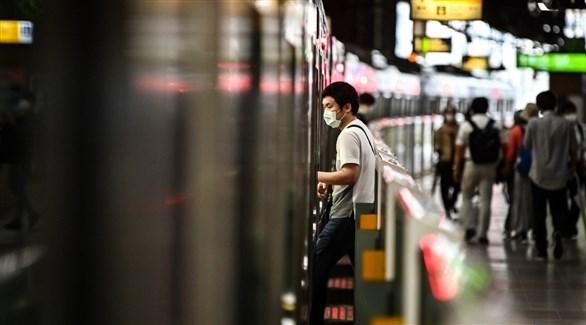 شخص يرتدي كمامة أثناء صعوده القطار (أرشيف)