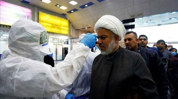 عامل في القطاع الصحي العراقي يتأكد من حرارة مسافر في مطار بغداد (أرشيف)