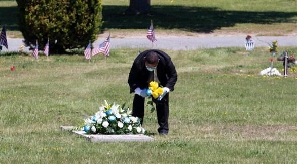 أمريكي يضع وروداً على قبر متوفى بكورونا (إ ب أ)
