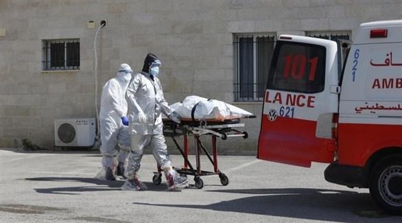 مسعفان فلسطينيان ينقلان جثة متوفى بكورونا لسيارة الإسعاف (إ ب أ)