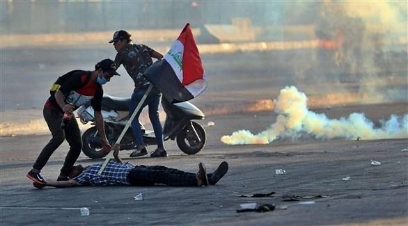 متظاهران عراقيان يحاولان إسعاف مصاب خلال احتجاجات في بغداد (أرشيف)
