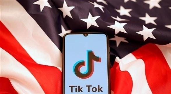 تطبيق تيك توك الصيني يظهر على شاشة هاتف موضوع فوق علم أمريكا (أرشيف)