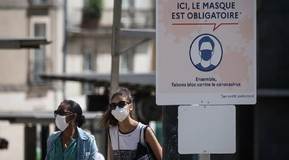 فرنسيتان تحت لافتة تطالب بوضع الكمامة في باريس (أرشيف)