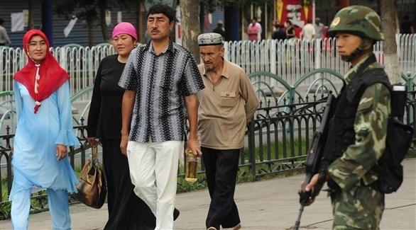 جندي صيني يراقب مسلمين من أقلية الويغور (أرشيف)