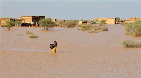 طفل سوداني يعبر مياه الفيضانات التي غمرت منزله للوصول إلى بر أمان (تويتر)