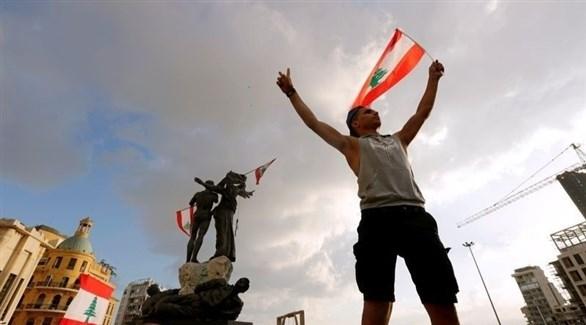 متظاهر يرفع العلم اللبناني في بيروت (أرشيف)