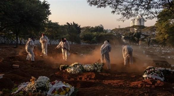 عاملون بقطاع الصحة البرازيلي يوارون جثمان متوفى بكورونا الثرى (أرشيف)