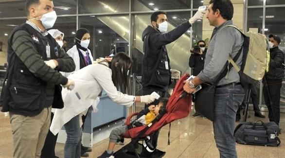 عاملان في القطاع الصحي المصري يفحصان مسافراً في مطار القاهرة الدولي (أرشيف)