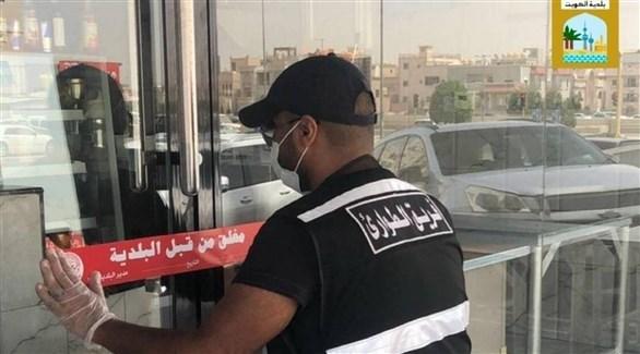 موظف في بلدية الكويت يُغلق محلاً مخالفاً لإجراءات الوقاية من كورونا (بلدية الكويت)