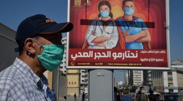 مغربي أمام لوحة إشهارية تدعو إلى احترام الحجر الصحي في الدار البيضاء (أرشيف)