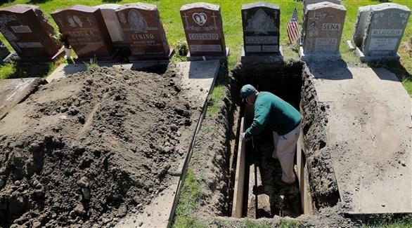 عامل في مقبرة أمريكية يجهز قبراً (أرشيف)